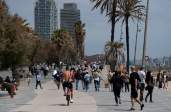 People walk near the beach of Barcelona, on May 9, 2021. - Spain has lifted a state of emergency in place since October to fight the pandemic, allowing Spaniards to travel between regions for the first time in months. (Photo by Josep LAGO / AFP)