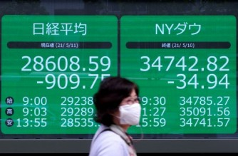 A pedestrian walks past an electronic quotation board displays the closing numbers of share price at the Tokyo Stock Exchange (L) in Tokyo on May 11, 2021. (Photo by Kazuhiro NOGI / AFP)