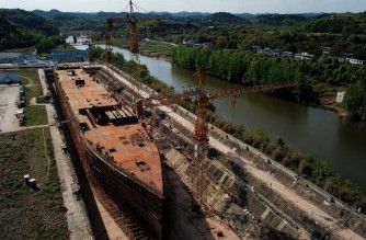This aerial photo taken on April 26, 2021 shows a still-under-construction replica of the Titanic ship in Daying County in China's southwest Sichuan province. - The ill-fated Titanic which sank over a hundred years ago is being resurrected as the centrepiece of a theme park in southwest China, where tourists can splash out for a night on the true-to-size vessel. (Photo by NOEL CELIS / AFP) / TO GO WITH China-society-tourism-Titanic,FOCUS by Noel Celis and Qian Ye