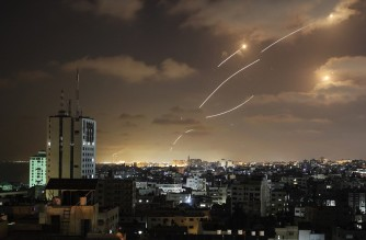Rockets launched from the Gaza Strip, controlled by the Palestinian Hamas movement, are intercepted by Israel's Iron Dome aerial defence system on May 12, 2021. (Photo by MAHMUD HAMS / AFP)