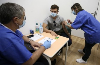 A 21-year-old man receives a dose of the Comirnaty vaccine by Pfizer-BioNTech against Covid-19 at the Baleone vaccine center in Ajaccio on the French Mediterranean island of Corsica, on May 13, 2021. - Vaccination is opened for people over 18 years old since early May in Corsica. The island has the highest vaccination rate in France. (Photo by Pascal POCHARD-CASABIANCA / AFP)