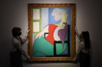 "(FILES) In this file photo taken on April 22, 2021 gallery workers display an artwork titled 'Femme assise près d'une fenêtre (Marie-Thérèse)' by Spanish painter Pablo Picasso during a photocall at Christie's auction house in central London. - Pablo Picasso's ""Woman sitting by a window (Marie-Therese)"" sold Thursday for $103.4 million at Christie's in New York, the auction house said. The painting, completed in 1932, was sold for $90 million, which rose to $103.4 million when fees and commissions were added, after 19 minutes of bidding, Christie's said. (Photo by DANIEL LEAL-OLIVAS / AFP) / RESTRICTED TO EDITORIAL USE - MANDATORY MENTION OF THE ARTIST UPON PUBLICATION - TO ILLUSTRATE THE EVENT AS SPECIFIED IN THE CAPTION"