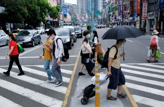 Pedestrians, wearing face masks after Taiwan bumped up its alert level in some locations in the wake of a new wave of Covid-19 coronavirus infections, cross a street in New Taipei City on May 15, 2021. (Photo by Sam Yeh / AFP)