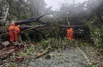 "This handout photo released on May 16, 2021 by the National Disaster Response Force (NDRF) shows National Disaster Response Force (NDRF) personnel clearing fallen trees from a road following severe cyclonic storm 'Tauktae' at Margao in Goa. (Photo by - / National Disaster Response Force (NDRF) / AFP) / RESTRICTED TO EDITORIAL USE - MANDATORY CREDIT ""AFP PHOTO / National Disaster Response Force (NDRF)"" - NO MARKETING - NO ADVERTISING CAMPAIGNS - DISTRIBUTED AS A SERVICE TO CLIENTS"