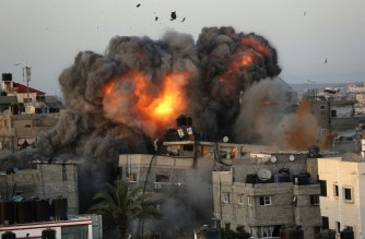A ball of fire erupts from a building in Gaza City's Rimal residential district on May 16, 2021, during massive Israeli bombardment on the Hamas-controlled enclave. (Photo by Bashar TALEB / AFP)