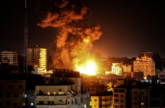 Fire and smoke rise above buildings in Gaza City as Israeli warplanes target the Palestinian enclave, early on May 17, 2021. (Photo by MAHMUD HAMS / AFP)