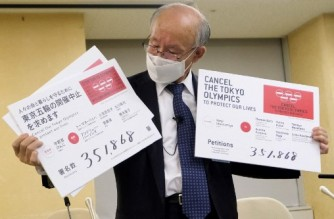 This picture taken on May 14, 2021 shows Kenji Utsunomiya, a Japanese lawyer and former Tokyo gubernatorial candidate, displaying posters of the petition calling for the cancellation of the Tokyo Olympics during his press conference at the Tokyo Metropolitan Government in Tokyo. (Photo by Kazuhiro NOGI / AFP)