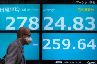 A man walks past an electronic quotation board displaying the closing numbers of share price at the Tokyo Stock Exchange in Tokyo on May 17, 2021. (Photo by Kazuhiro NOGI / AFP)