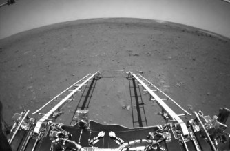 This picture released on May 19, 2021, by the China National Space Administration (CNSA) via CNS shows an image taken by the front obstacle avoidance camera of China's Zhurong rover, facing the rover's direction of movement and showing the deployment of the ramp mechanism, on the surface of Mars, after it landed on Mars on May 15, 2021. (Photo by - / CNS/CNSA / AFP) / China OUT
