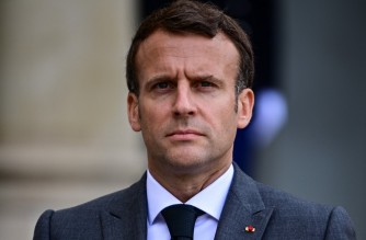 French President Emmanuel Macron looks on as NATO Secretary General talks to the press after a meeting to prepare the upcoming NATO summit, at the Elysee Palace in Paris, on May 21, 2021. (Photo by MARTIN BUREAU / AFP)