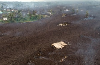 This aerial view shows debris engulfing buildings in Bushara village, Nyiragongo area, near Goma, on May 23, 2021, after a volcanic eruption of Mount Nyiragongo, that sent thousands fleeing during the night in eastern Democratic Republic of Congo. - A river of boiling lava from the eruption of Mount Nyiragongo has came to a halt outside Goma, sparing the city in the east of the Democratic Republic of Congo, the military governor of the region said on May 23, 2021. Five people were killed in related accidents. (Photo by Justin KATUMWA / AFP)