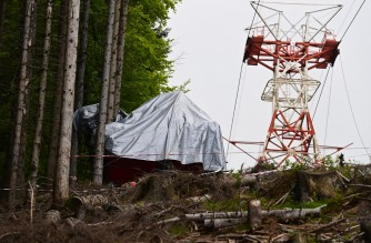 A view shows the cabin's wreckage covered with a tarpaulin next to a pylon on May 26, 2021 on the slopes of the Mottarone peak above Stresa, Piedmont, three days after a cable car crash that killed 14. - Investigators probed the causes of a terrifying cable car crash in the Italian mountains that left 14 people dead, including five Israelis, and a young child fighting for life. (Photo by MIGUEL MEDINA / AFP)