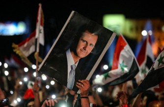 Syrians wave national flags and carry a portrait of their president as they celebrate in the streets of the capital Damascus, a day after an election set to give the current President Bashar al-Assad a fourth term, on May 27, 2021. - The election held yesterday in government-held areas was the second presidential vote in Syria since the start in 2011 of a war that has left over 388,000 dead. (Photo by LOUAI BESHARA / AFP)