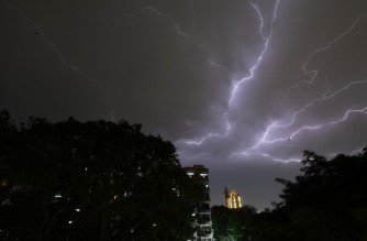 Lightning strikes over residential apartments during a thunderstorm on the outskirts of the Indian capital New Delhi on May 2, 2018. - Dust storms tore across northern India killing at least 77 people and injuring 143 as trees and walls were flattened by powerful winds, officials said May 3. (Photo by PRAKASH SINGH / AFP)