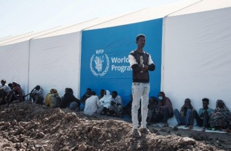 Ethiopian refugees who fled the Ethiopia's Tigray conflict wait for distribution of aid next to a warehouse erected by the World Food Programme (WFP) at Um Raquba refugee camp in Gedaref, eastern Sudan, on December 6, 2020. - More than 45,000 people have escaped from northern Ethiopia since November 4, after Prime Minister Abiy Ahmed ordered military operations against leaders of Tigray's ruling party in response to its alleged attacks on federal army camps. (Photo by Yasuyoshi CHIBA / AFP)