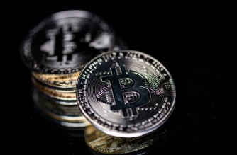 This photograph taken on April 26, 2021 in Paris shows a physical imitation of the Bitcoin crypto currency. (Photo by Martin BUREAU / AFP)