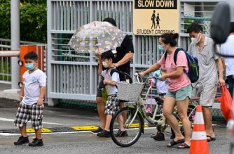 Children walk home with their guardians after school in Singapore on May 17, 2021, as the country prepares to shut all schools and switch to home-based learning until the end of the term due to a rise in the number of Covid-19 coronavirus cases. (Photo by Roslan RAHMAN / AFP)