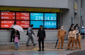 People stand in front of an electronic quotation board displaying the closing numbers of share price at the Tokyo Stock Exchange in Tokyo on May 17, 2021. (Photo by Kazuhiro NOGI / AFP)
