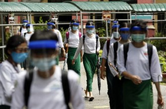 (FILES) In this file photo taken on July 21, 2020 atudents wearing masks and face shields leave after attending classes during the first day of reopening of public high schools following closures due to the spread of the COVID-19 coronavirus in Yangon. - Myanmar junta ministers have been busy cutting ribbons and handing out textbooks to parents during school enrolment week, but when term begins on June 1, 2021, many classrooms will be empty as teachers and students stay away to protest military rule. (Photo by Sai Aung Main / AFP)