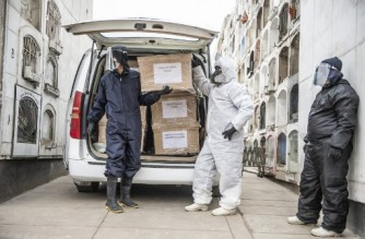 (FILES) In this file photo taken on May 21, 2020, workers stand next to coffins of COVID-19 victims at El Angel cemetery, in Lima. - Peru has adjusted its official coronavirus death toll upward by almost a third from 69,000 to more than 180,000, the government said on May 31, 2021. (Photo by ERNESTO BENAVIDES / AFP)
