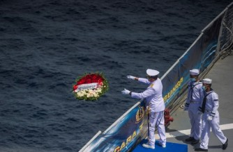 (FILES) In this file photo taken on April 30, 2021, a naval officer throws a flower bouquet into the sea during a remembrance ceremony for the crew of the Indonesian navy submarine KRI Nanggala that sank on April 21 during a training exercise, on the deck of the hospital ship KRI Dr. Soeharso off the coast of Bali. - Indonesia has called off its bid to salvage a military submarine that sank off the coast of Bali, killing all 53 crew aboard, the navy said on June 2, 2021. (Photo by Juni Kriswanto / AFP)