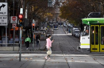 People cross Melbourne's normally bustling Bourke Street Mall on June 4, 2021, as the coronavirus lockdown of Australia's second-biggest city is extended by another seven days, authorities announced. (Photo by William WEST / AFP)