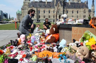"""(FILES) In this file photo taken on June 1, 2021 Canadian Prime Minister Justin Trudeau visits the makeshift memorial erected in honor of the 215 indigenous children remains found at a boarding school in British Columbia, on Parliament Hill in Ottawa. - Canadian Prime Minister Justin Trudeau on June 4, 2021 urged the Catholic Church to """"take responsibility"""" and release records on indigenous residential schools under its direction, after the discovery of remains of 215 children in unmarked graves. (Photo by Dave Chan / AFP)"""
