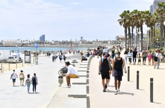 People walk on the promenade at Bogatell Beach on June 6, 2021 in Barcelona. - Spain will allow all vaccinated travellers to visit the country from June 7, as the tourism hotspot aims to revive its virus-battered travel industry. (Photo by Pau BARRENA / AFP)