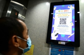 A man looks at a display screen inside an elevator asking for public donation to Vietnam's national fund for Covid-19 coronavirus vaccine in Hanoi on June 8, 2021, as the country struggles to contain a new coronavirus wave. (Photo by Nhac NGUYEN / AFP)