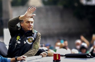 Brazilian President Jair Bolsonaro waves as he leads a motorcade rally with supporters in Sao Paulo, Brazil, on June 12, 2021. - Bolsonaro was fined $100 Saturday for violating Covid-19 containment measures in Sao Paulo state by failing to wear a face mask and provoking huge crowds at a motorcycle rally for supporters. (Photo by Miguel SCHINCARIOL / AFP)