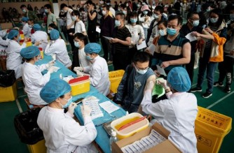 (FILES) This file photo taken on April 28, 2021 shows university students queueing to receive the China National Biotec Group (CNBG) Covid-19 coronavirus vaccine at a university in Wuhan, in China's central Hubei province. - China has now administered more than a billion doses of Covid vaccines, the country's health authority said on June 20, 2021, more than a third of the number given worldwide. (Photo by STR / AFP) / China OUT