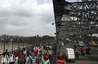 Commuters walk while crossing the Howrah Bridge as the state government suspended regular public transport during a lockdown imposed to curb the spread of the Covid-19 coronavirus, in Kolkata on June 23, 2021. (Photo by Dibyangshu SARKAR / AFP)