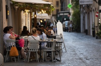 People sit at an outside table at a bar on the eve of Italy moving into the 'white zone' when it will not be obligatory to wear the mask outdoors in Rome on June 27, 2021. (Photo by Tiziana FABI / AFP)