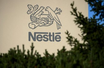 A logo of the world's leading food industry group Nestle is seen on October 9, 2014 at the group's Research Center in Vers-chez-les-Blanc above Lausanne.  AFP PHOTO / FABRICE COFFRINI (Photo by FABRICE COFFRINI / AFP)