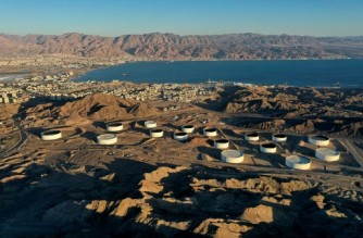 """This picture taken on February 10, 2021 shows an aerial view of (foreground) oil storage containers of the Eilat Ashkelon Pipeline Company (EAPC) in the mountains near Israel's Red Sea port city of Eilat (C-L), and (background) the Jordanian coastline south of Aqaba (top L). - Israeli environmentalists are warning that the UAE-Israeli deal to bring Emirati crude oil by tanker to a pipeline in Eilat threatens unique Red Sea coral reefs and could lead to """"the next ecological disaster"""". The deal was signed after Israel and the UAE normalised ties late in 2020, and should come into force within the next few months. (Photo by MENAHEM KAHANA / AFP)"""