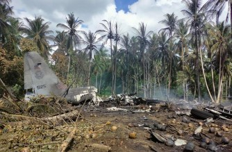 """In this handout photo taken on July 4, 2021 and received from the Philippine military Joint Task Force-Sulu (JTF-Sulu), smoke billows from the wreckage of a Philippine Airforce C-130 transport plane after it crashed near the airport in Jolo town, Sulu province on the southern island of Mindanao. (Photo by Handout / Joint Task Force-Sulu / AFP) / -----EDITORS NOTE --- RESTRICTED TO EDITORIAL USE - MANDATORY CREDIT """"AFP PHOTO / JOINT TASK FORCE-SULU (JTF-SULU) """" - NO MARKETING - NO ADVERTISING CAMPAIGNS - DISTRIBUTED AS A SERVICE TO CLIENTS"""