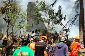 """In this handout photo taken on July 4, 2021 and received from the Philippine military Joint Task Force-Sulu (JTF-Sulu), rescue workers arrive as smoke billows from the wreckage of a Philippine Airforce C-130 transport plane after it crashed near the airport in Jolo town, Sulu province on the southern island of Mindanao. (Photo by Handout / Joint Task Force-Sulu / AFP) / -----EDITORS NOTE --- RESTRICTED TO EDITORIAL USE - MANDATORY CREDIT """"AFP PHOTO / JOINT TASK FORCE-SULU (JTF-SULU) """" - NO MARKETING - NO ADVERTISING CAMPAIGNS - DISTRIBUTED AS A SERVICE TO CLIENTS"""