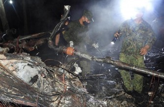 """In this handout photo taken on July 4, 2021, received from Philippine military Joint Task Force-Sulu (JTF-SULU) on July 5, soldiers inspect the wreckage of the ill-fated Philippine Airforce C-130 transport that crashed near the airport in Jolo town, Sulu province, in southern island of Mindanao, during the search and retrieval operations. (Photo by Handout / JOINT TASK FORCE-SULU / AFP) / -----EDITORS NOTE --- RESTRICTED TO EDITORIAL USE - MANDATORY CREDIT """"AFP PHOTO / JOINT TASK FORCE-SULU (JTF-SULU) """" - NO MARKETING - NO ADVERTISING CAMPAIGNS - DISTRIBUTED AS A SERVICE TO CLIENTS"""