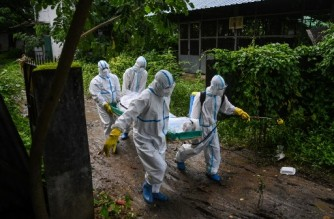 Volunteers wearing personal protective equipment (PPE) carry the body of a victim of the Covid-19 coronavirus to a cemetery in Hlegu Township in Yangon on July 10, 2021. (Photo by Ye Aung THU / AFP)