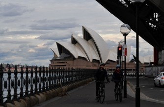 Cyclists ride along a quiet walkway under the Harbour Bridge in Sydney on July 19, 2021, amid a lockdown in Melbourne and Sydney as Australia seeks to contain a surge in coronavirus cases. (Photo by Saeed KHAN / AFP)