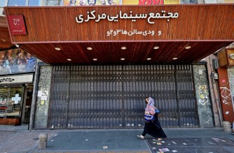 Iranians walk past a shuttered cinema hall in downtown Tehran on July 20, 2021. - Iran a day earlier announced strict curbs in the capital Tehran and a nearby province to stem the spread of Covid-19, as daily infections drew close to an all-time high. (Photo by ATTA KENARE / AFP)