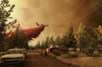 """This photo provided by the Oregon Department of Forestry shows a firefighting tanker droping a retardant over the Grandview fire near Sisters, Oregon on July 11, 2021. (Photo by Handout / Oregon Department of Forestry / AFP) / RESTRICTED TO EDITORIAL USE - MANDATORY CREDIT """"AFP PHOTO /Oregon Department of Forestry"""" - NO MARKETING - NO ADVERTISING CAMPAIGNS - DISTRIBUTED AS A SERVICE TO CLIENTS"""