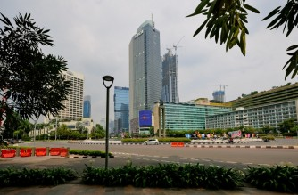 A lone car circles a main roundabout in the quiet city centre in Jakarta on July 24, 2021, two days before the planned reopening of the capital after nearly three weeks of restrictions due to the COVID-19 coronavirus. (Photo by BAY ISMOYO / AFP)