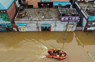 This aerial photo taken on July 23, 2021 shows rescue workers evacuating residents following heavy rains in Xinxiang, in China's central Henan province. (Photo by - / AFP) / China OUT