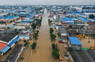 This aerial photo taken on July 23, 2021 shows flooded buildings and streets following heavy rains in Xinxiang, in China's central Henan province. (Photo by - / AFP) / China OUT
