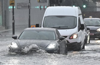 Cars drive through deep water on a flooded road in The Nine Elms district of London on July 25, 2021 during heavy rain. - Buses and cars were left stranded when roads across London flooded on Sunday, as repeated thunderstorms battered the British capital. (Photo by JUSTIN TALLIS / AFP)