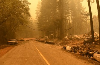 Downed power lines lay across a road as burned vehicles smolder during the Dixie fire in the Indian Falls area of unincorporated Plumas County on July 25, 2021. - The Dixie fire has now burned more than 190,000 acres and continues to edge closer to more residential communities. (Photo by JOSH EDELSON / AFP)
