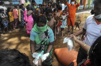 India's National Disaster Response Force (NDRF), personnel distribute food and relief materials to people in areas inundated with flood waters at Sangli district of Maharashtra. (Photo by Uday Deolekar / AFP)