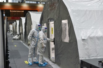 """This photo taken on July 28, 2021 shows staff members checking a unit at a temporary """"Fire Eye"""" laboratory used for Covid-19 coronavirus testing at an exhibition centre in Nanjing in China's eastern Jiangsu province. (Photo by STR / AFP) / China OUT"""