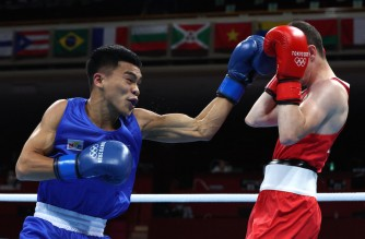 Ireland's Brendan Irvine (red) and Philippines' Carlo Paalam fight during their men's fly (48-52kg) preliminaries boxing match during the Tokyo 2020 Olympic Games at the Kokugikan Arena in Tokyo on July 26, 2021. (Photo by Buda Mendes / POOL / AFP)